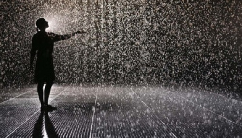 LONDON, ENGLAND - OCTOBER 03:  A woman experiences the 'Rain Room' art installation by 'Random International' in The Curve at the Barbican Centre on October 3, 2012 in London, England. The 'Rain Room' is a 100 square meter field of falling water which visitors are invited to walk into with sensors detecting where the visitor are standing. The installation opens to the public on October 4, 2012 and runs until March 3, 2013.  (Photo by Oli Scarff/Getty Images)